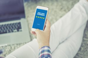 Woman rating a service on a hotel booking app on her phone