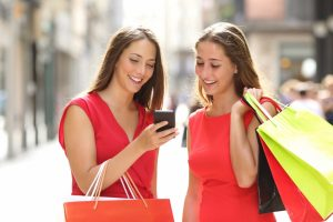 girls looking at their phone while shopping