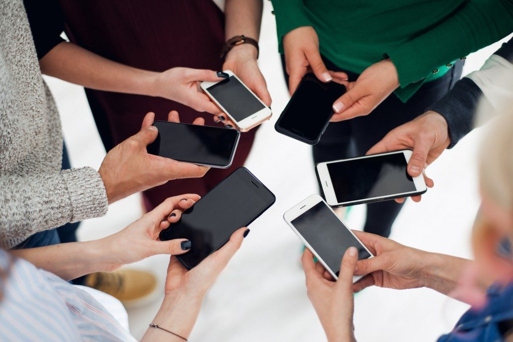 colleagues using their smartphones in a huddle