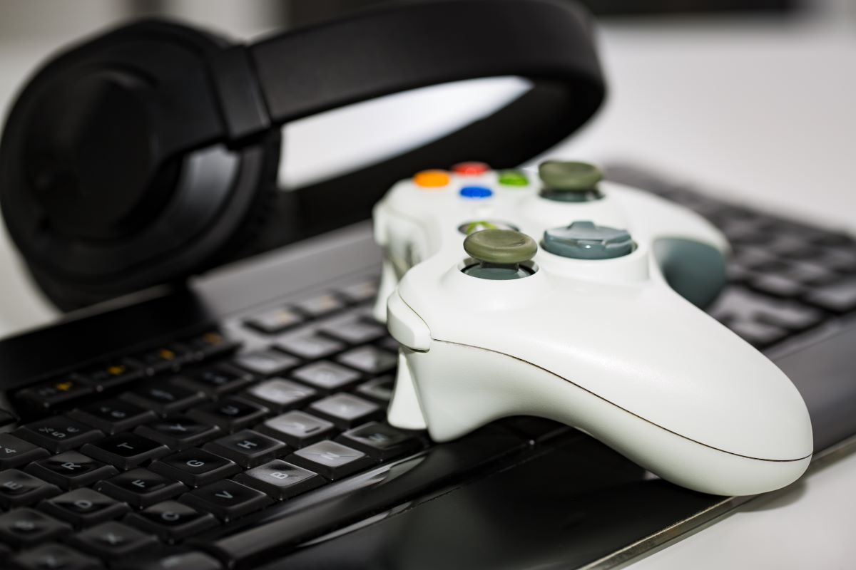 video game controller on a keyboard and a pair of headset